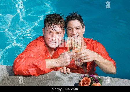 Entièrement vêtu gay couple drinking champagne in swimming pool Photo Stock