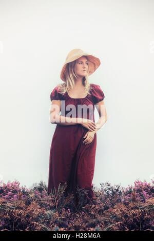 Une femme en robe rouge est debout dans la bruyère Photo Stock