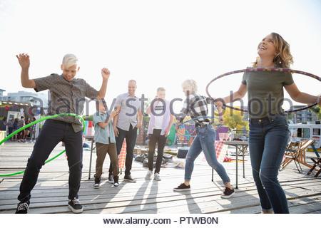 Famille ludique de la vrille en plastic hoops au carnaval Photo Stock