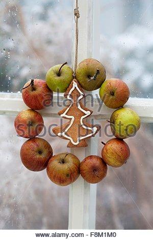 Un identifiant Apple et une couronne de Noël suspendus dans la fenêtre Photo Stock