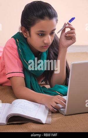 Portrait de l'espace rural girl lying on floor using laptop et étudier Photo Stock