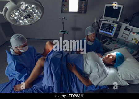 High angle view of Caucasian female surgeon examining pregnant Caucasian woman lors de l'accouchement tandis que l'homme tenait la main dans la salle d'opération à hospital Photo Stock