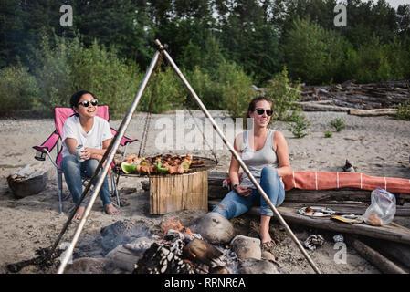 Les femmes bénéficiant de détente, barbecue sur la plage Photo Stock