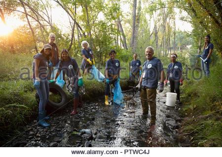 Portrait confiant bénévoles, le nettoyage des ordures dans le ruisseau Photo Stock