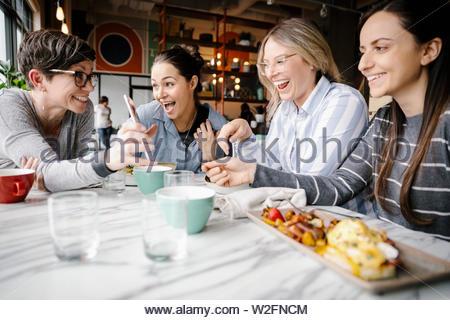Happy women friends with camera phone manger dans restaurant Photo Stock