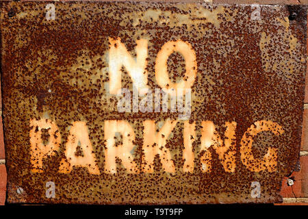 Old rusty metal no parking sign on wall Photo Stock