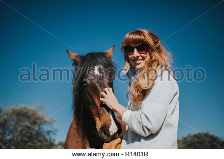 Une jeune femme avec un cheval dans le soleil Photo Stock