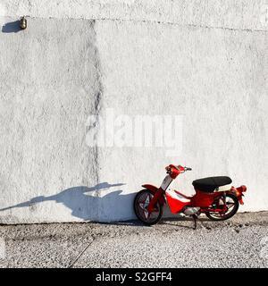 Scooter rouge et blanc mur dans île de Milos, Grèce Photo Stock