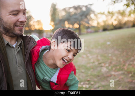 Happy father and son playing in autumn park Photo Stock