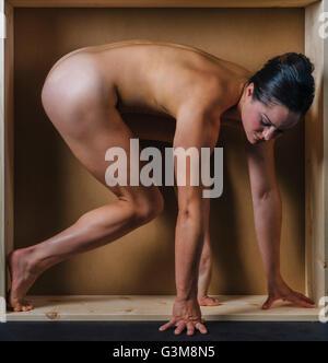 Femme nue à quatre pattes à la case Photo Stock