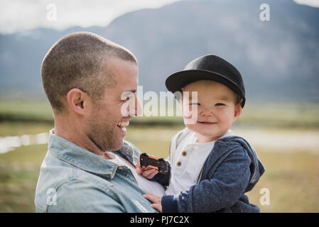 Père holding cute, happy baby son looking at camera Photo Stock