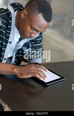 Dix-huit ans homme assis à un bureau et à l'aide d'un ipad. Photo Stock