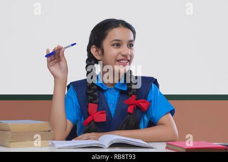 Portrait of smiling girl in school uniform looking away holding pen Photo Stock
