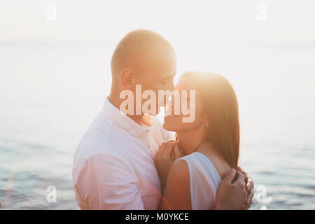 Caucasian couple hugging près de ocean at sunset Photo Stock