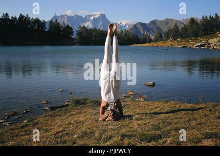 Woman practicing yoga at mountain lakeshore. Position Shirsasana Photo Stock