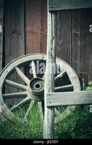 Vieille roue de chariot à l'extérieur du mur du bâtiment rural. Nostalgie rustique en bois objet. Photo Stock