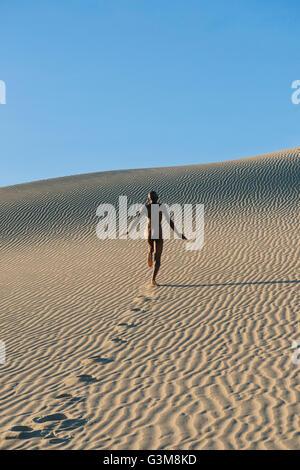 Femme nue s'exécutant dans le dessert laissant footprints Photo Stock