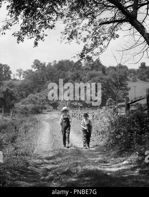Années 1930 DEUX GARÇONS WALKING DOWN COUNTRY LANE EXERÇANT SON STICK de cannes à pêche sur l'ÉPAULE PORTANT SALOPETTE - UN2492 HAR001 SALOPETTE DE PÊCHE DE LA STATION DE PRÉ-ADO PRÉ-ADO GARÇON NOIR ET BLANC ENSEMBLE BIELLES Origine ethnique Caucasienne HAR001 old fashioned Photo Stock