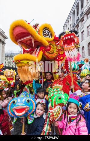 L'Angleterre, Londres, le quartier chinois, le Nouvel An chinois défilé, Parade des participants détenant Dragon chinois Photo Stock
