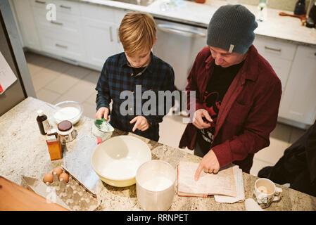 Père et fils, la cuisson à la recette de cuisine à en Photo Stock
