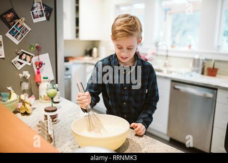 Le Tween boy baking in kitchen Photo Stock