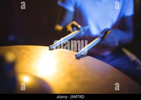 Section intermédiaire de batteur jouant tambour en discothèque Photo Stock