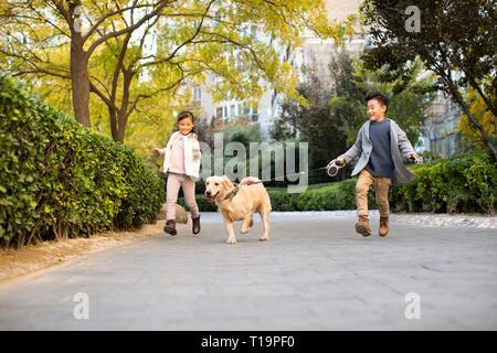 Deux enfants courir avec chien Photo Stock