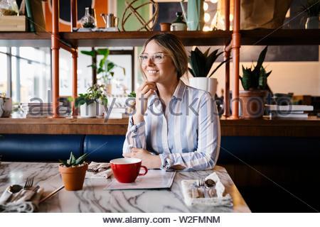 Confiant, Portrait smiling woman at cafe table Photo Stock