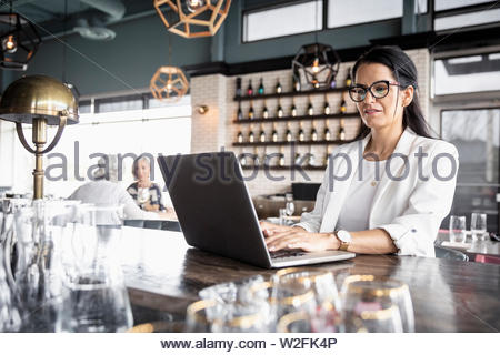 Businesswoman working at laptop in bar Photo Stock