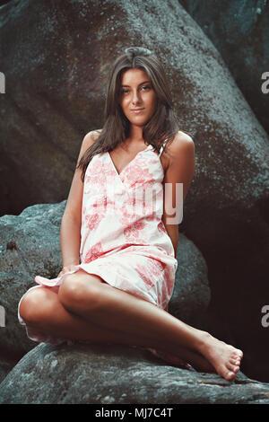 Belle jeune fille avec robe d'été sur les pierres de rivière Photo Stock