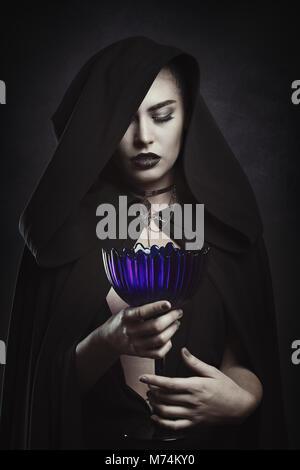 Belle vampire avec une coupe rituelle. La figure à capuchon Photo Stock