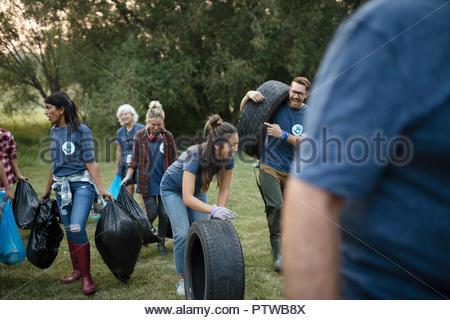 Bénévoles, le nettoyage des ordures dans park et roulement des pneumatiques Photo Stock