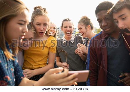 Les adolescents ludique avec téléphone appareil photo et accessoires moustache Photo Stock