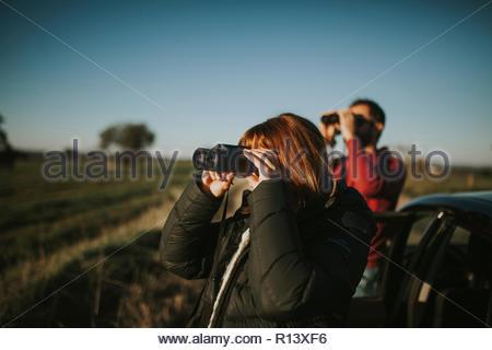 Une femme à l'aide de jumelles dans un champ sur une journée ensoleillée Photo Stock