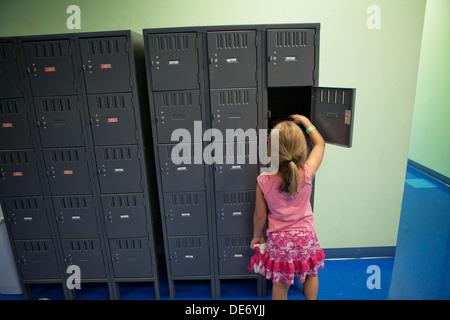 Fillette de huit ans ouvre son casier. Photo Stock