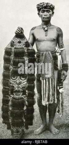 Jeune homme avec son bouclier, les Kenyah, Bornéo, l'Asie du Sud-Est (alors partie de l'Empire britannique). Il a un visage stylisé peint sur elle, et est décoré avec des cheveux de ses victimes. Photo Stock