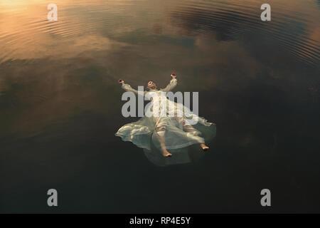 Jeune fille morte flottant dans les eaux du lac Photo Stock