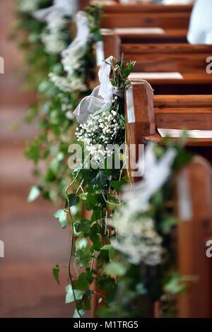 Allée de l'église est décorée de lierre et de fleurs blanches pour un mariage Photo Stock