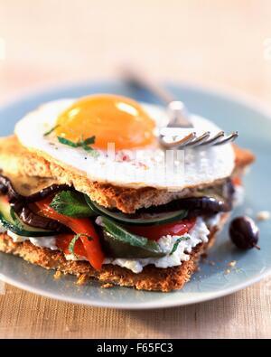 Sandwich grillé avec des oeufs frits, légumes et fromage de chèvre Photo Stock