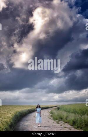 Une femme dans une robe bleue marche sur un chemin à travers les champs sous les nuages de tempête Photo Stock