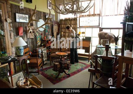 Femme boutiques dans un magasin d'antiquités, USA. Photo Stock