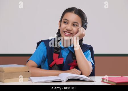 La fille rurale dans l'uniforme scolaire à l'écart pendant ses études en classe Photo Stock