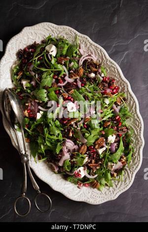 Roquette, grenade et salade de riz noir sur un ovale plat de service. Photo Stock
