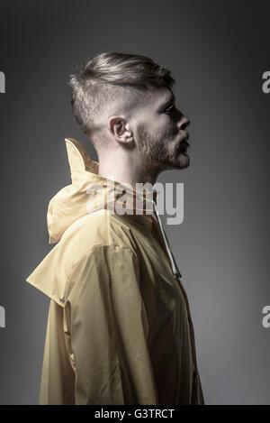Studio portrait d'un jeune homme barbu dans un vent jaune tricheur. Photo Stock