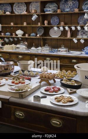 Le tableau dans la cuisine avec des ustensiles et des pâtisseries en charge avec la commode derrière à Photo Stock