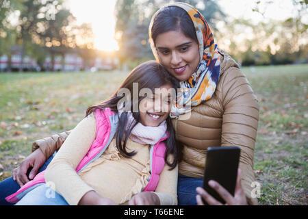 Mère musulmane en hijab en tenant avec selfies fille in autumn park Photo Stock