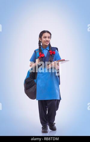 Portrait de jeune fille rurale dans l'uniforme scolaire à loin sitting at table Photo Stock