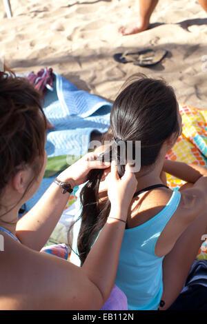 Teenage girl tressage des cheveux pour un ami sur la plage. Photo Stock