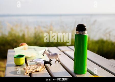 Verre isolé contenant et jouets sur une table de pique-nique Photo Stock