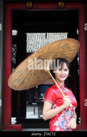 Femme portant robe tradition vietnamienne appelée Ao Dai, temple taoïste, une pagode de Phuoc Hoi Quan, Ho Chi Minh City, Vietnam, Indochine, Asie du sud-est, Photo Stock